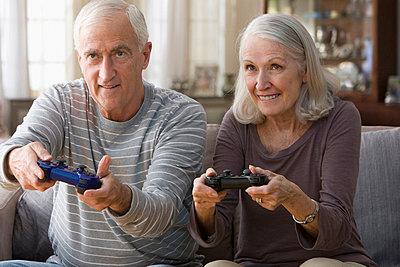 Senior couple playing video game - p924m711229f by Jose Luis Pelaez Inc.