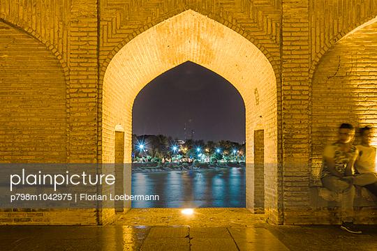 Junge Männer sitzen abends auf der Si-o-se Pol Brücke, Esfahan, Iran - p798m1042975 von Florian Loebermann