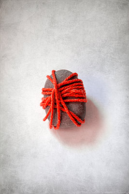 Pebble wrapped in a red string  - p1248m2270300 by miguel sobreira