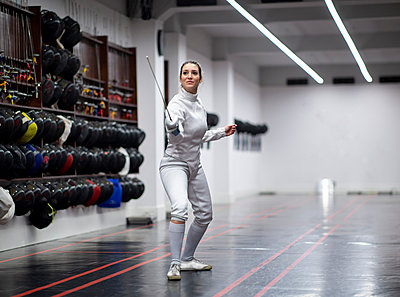 Woman in fencing outfit practicing at gym - p300m2243585 by Jose Carlos Ichiro
