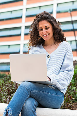 Smiling woman using laptop while sitting on retaining wall - p300m2277402 by NOVELLIMAGE