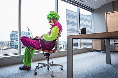 Caucasian businessman wearing clown costume in office - p555m1305931 by Hill Street Studios