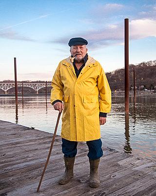 Older Caucasian fisherman standing on dock - p555m1491166 by Tom M Johnson
