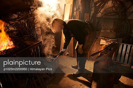 Female blacksmith working in workshop - p1023m2200950 by Himalayan Pics
