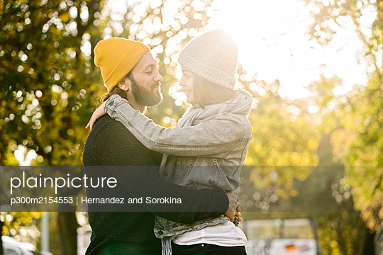 Young couple embracing in a city park at sunset, Berlin, Germany - p300m2154553 by Hernandez and Sorokina
