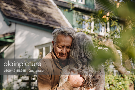 Senior man hugging his wife in garden of their home in autumn - p300m2156245 by Gustafsson