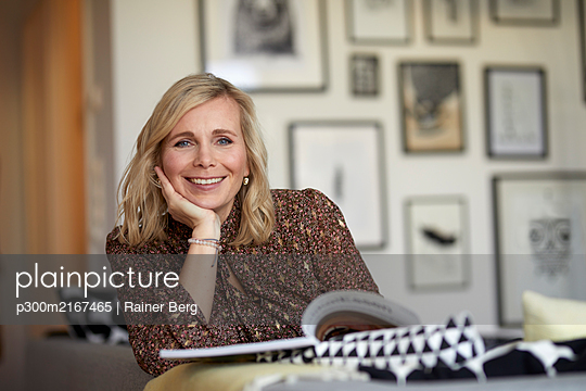 Portait of blond woman relaxing at home sitting on couch - p300m2167465 by Rainer Berg