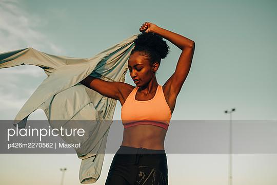 Female athlete wearing jacket against sky during sunset - p426m2270562 by Maskot