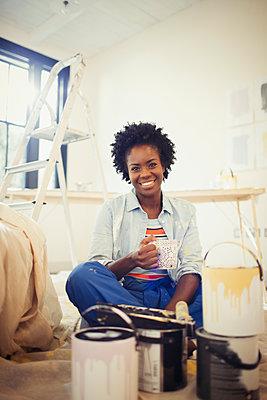 Portrait smiling woman drinking coffee, painting living room - p1023m1519997 by Paul Bradbury