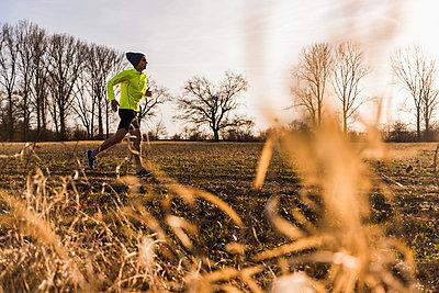 Man running in rural landscape - p300m1356374 by Uwe Umstätter