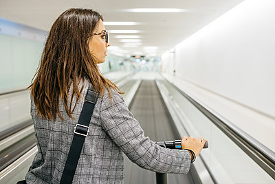 Businesswoman with her electric scooter on moving walkway - p300m2155396 by Josep Rovirosa