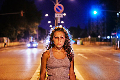 Portrait of teenage girl in the middle of the road looking at camera - p429m1418111 by Bruno Gori