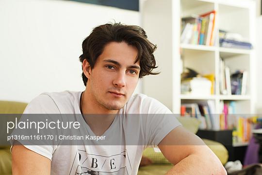 Junger Mann sitzt auf dem Sofa, Nachdenklich - p1316m1161170 von Christian Kasper