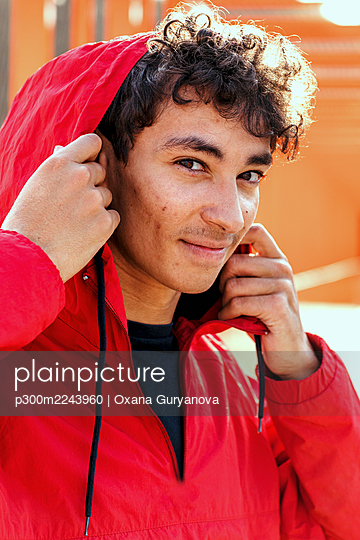 Close-up portrait of smiling young man wearing red hood - p300m2243960 by Oxana Guryanova