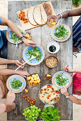 Overhead view of friends having lunch at outdoor table - p1166m1151265 by Cavan Images
