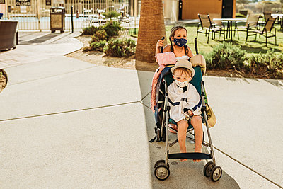 Young children in stroller leaving pool with masks on vacation - p1166m2218283 by Cavan Images