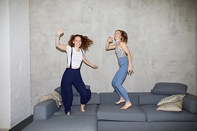 Girlfriends jumping around on sofa  - p276m2115596 by plainpicture