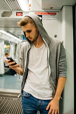 Young man using smartphone in metro - p300m2058948 by Josep Rovirosa