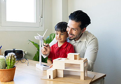 Smiling male architect showing turbine model to son at home office - p300m2282154 by Jose Carlos Ichiro