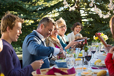 Family enjoying an outdoor meal together. - p328m784056f by Hero Images