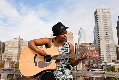 Mature woman playing guitar in front of Philadelphia skyline, USA - p429m1084510 by Zave Smith