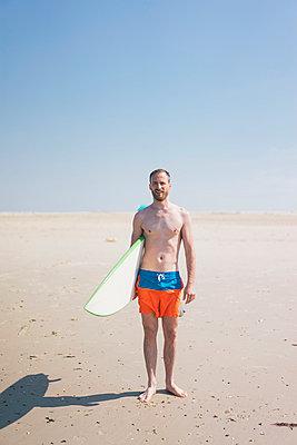 Mann mit Surfbrett am Strand - p586m1041267 von Kniel Synnatzschke