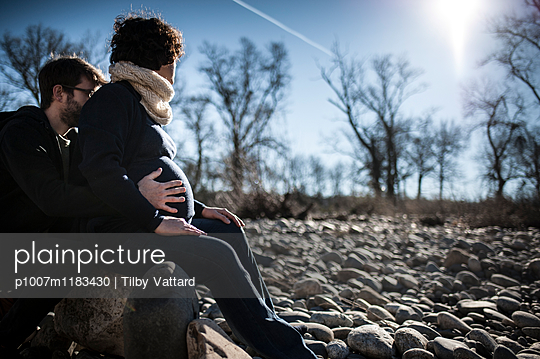 Young couple waiting for a baby siting on a stone looking at the sun - p1007m1183430 by Tilby Vattard
