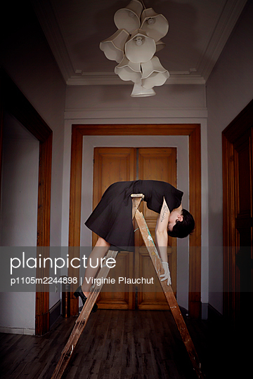 Woman in black dress on a ladder - p1105m2244898 by Virginie Plauchut