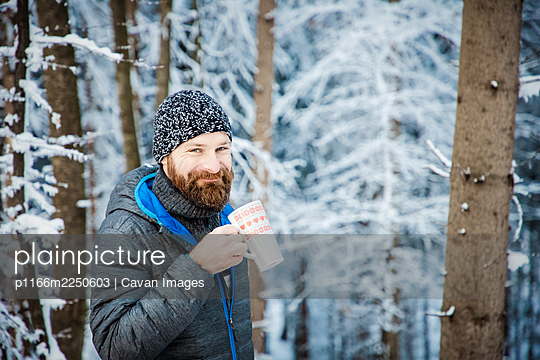 man drinking hot tea in winter forest - p1166m2250603 by Cavan Images