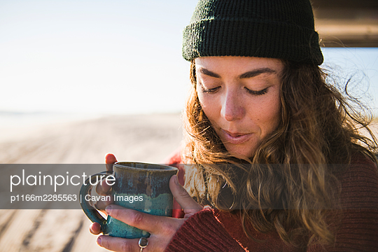 Young woman enjoying cup of coffee in the morning beach car camping - p1166m2285563 by Cavan Images