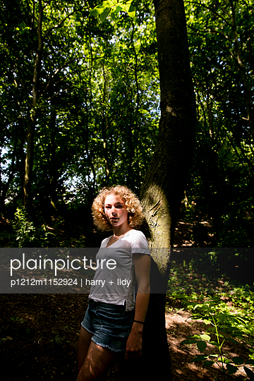 Mädchen lehnt an einem Baum im Wald - p1212m1152924 von harry + lidy