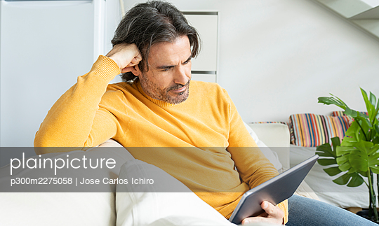 Man using digital tablet while sitting on sofa in living room - p300m2275058 by Jose Carlos Ichiro