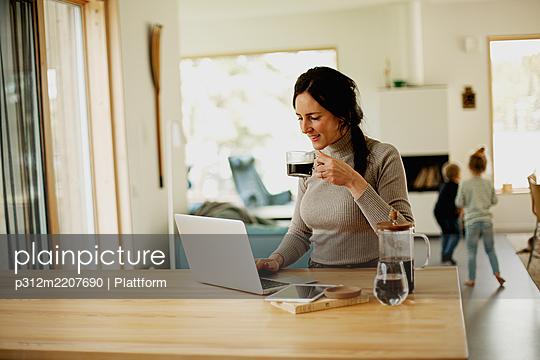 Woman using laptop at home - p312m2207690 by Plattform