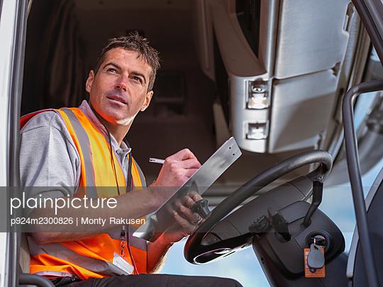 UK, Truck driver writing on clipboard in truck cabin - p924m2300826 by Monty Rakusen