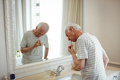 Senior man brushing his teeth - p1315m1230767 by Wavebreak