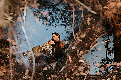 Young couple reflecting in small shiny puddle - p300m2241680 by Sara Monika