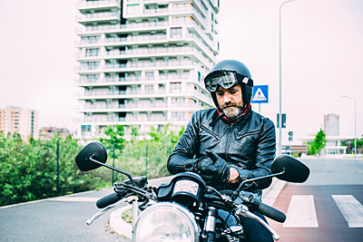 Mature male motorcyclist sitting on motorcycle putting on gloves - p429m1175487 by Eugenio Marongiu