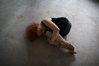 Caucasian woman laying on concrete in fetal position - p555m1523132 by Kateryna Soroka