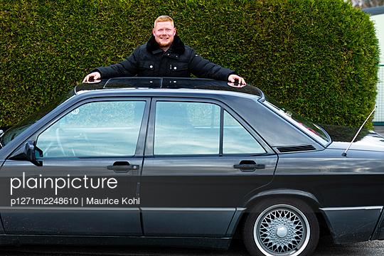 Mann steht vor seinem Auto, Portrait - p1271m2248610 von Maurice Kohl