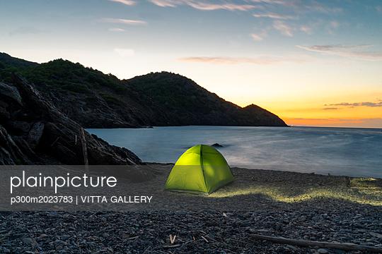Spain, Catalonia, Costa Brava, green tent at stony beach in the evening - p300m2023783 by VITTA GALLERY