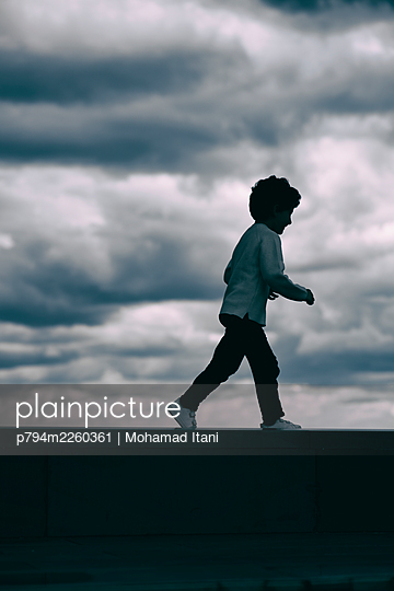 Side view of little boy running away outdoors  - p794m2260361 von Mohamad Itani
