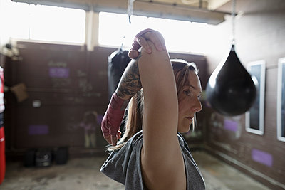 Female boxer stretching arm in gym - p1192m1447667 by Hero Images