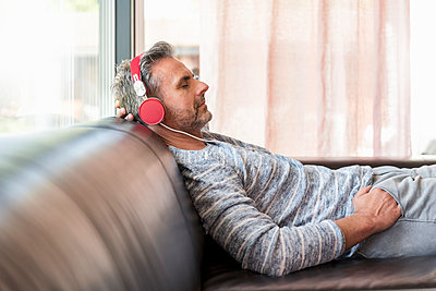 Relaxed mature man lying on couch at home wearing headphones - p300m2004778 von Daniel Ingold