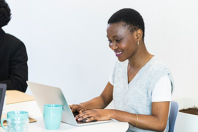 Smiling mid adult entrepreneur using laptop while working at office - p300m2277219 by NOVELLIMAGE