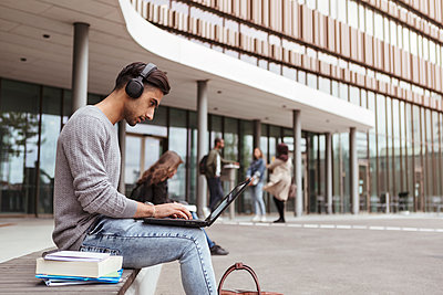 Young student listening music while using laptop at university campus - p426m2072229 by Kentaroo Tryman