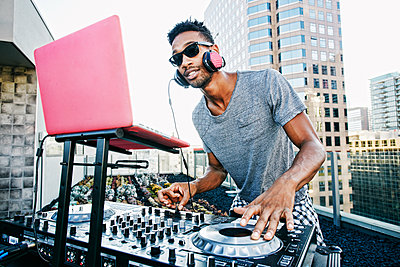 Smiling Black DJ on urban rooftop - p555m1301711 by Peathegee Inc