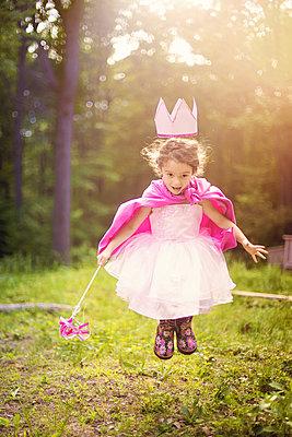 Girl playing princess in backyard - p555m1409485 by Shestock