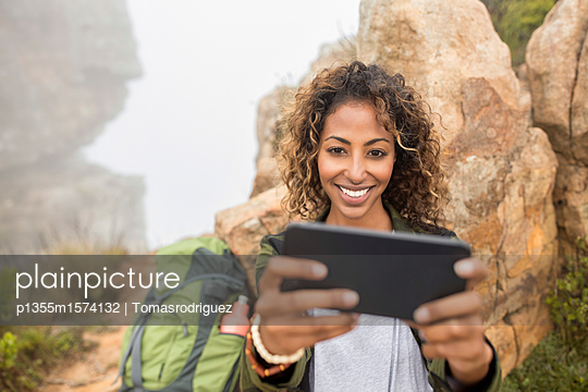 Junge Frau mit Tablet auf ihrer Bergtour - p1355m1574132 von Tomasrodriguez