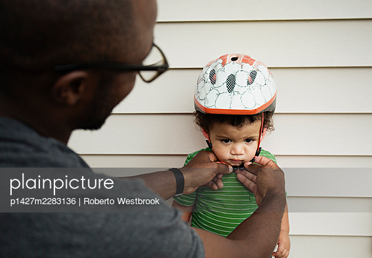 Father putting on helmet for son - p1427m2283136 by Roberto Westbrook
