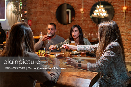 Friends having drink and food while sitting by table at restaurant - p300m2227013 by Oscar Carrascosa Martinez
